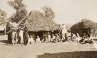 Aboriginal people outside thatched huts 1923