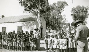 Children lined up outside schoolhouse