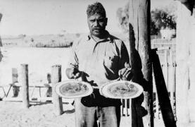 Albert Namatjira holding to painted mulga plaques at Hermannsburg 1939.